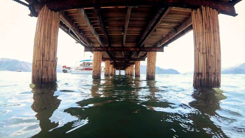 Vista de debaixo do cais de madeira em ondas do mar calmo fotos de stock royalty free