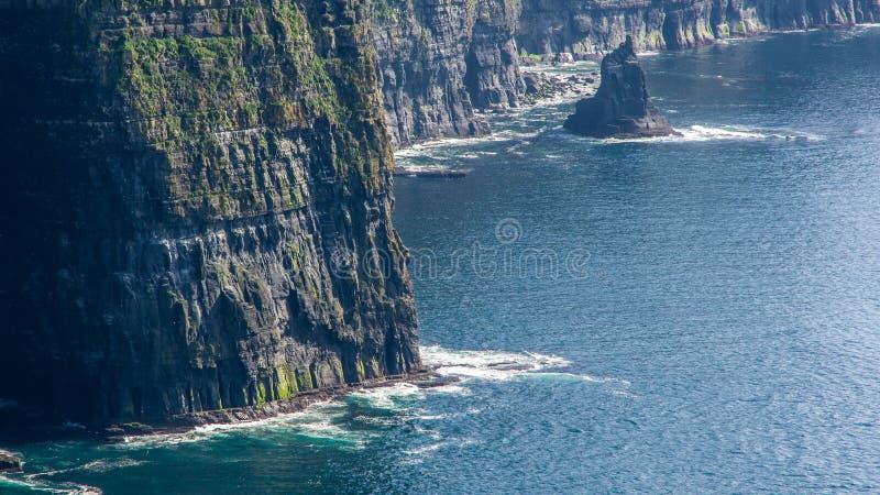 Vista de detalles del mar oscuro y de las ondas que rompen en las rocas acantilados fotografía de archivo libre de regalías