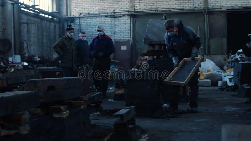 Vista de hombres en batas protectoras y de máscaras que trabajan en la planta de acería vieja Cantidad com?n Detalles industriale fotografía de archivo