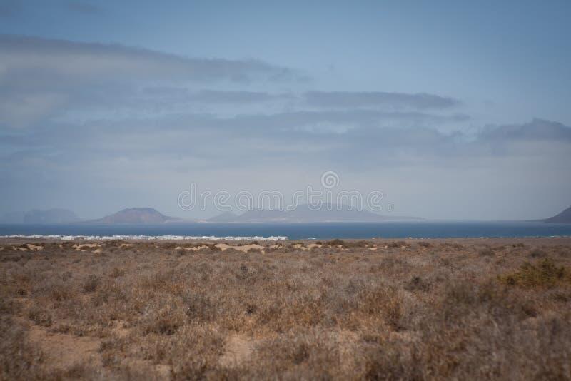 Vista de Ilhas Canárias de Lanzarote da praia de Famara fotografia de stock royalty free