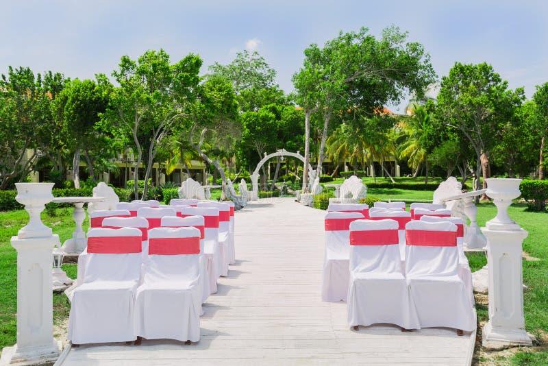 Vista de invitación bonita de un jardín tropical con las sillas cómodas acogedoras blancas adornadas, preparada para una ceremoni imagenes de archivo