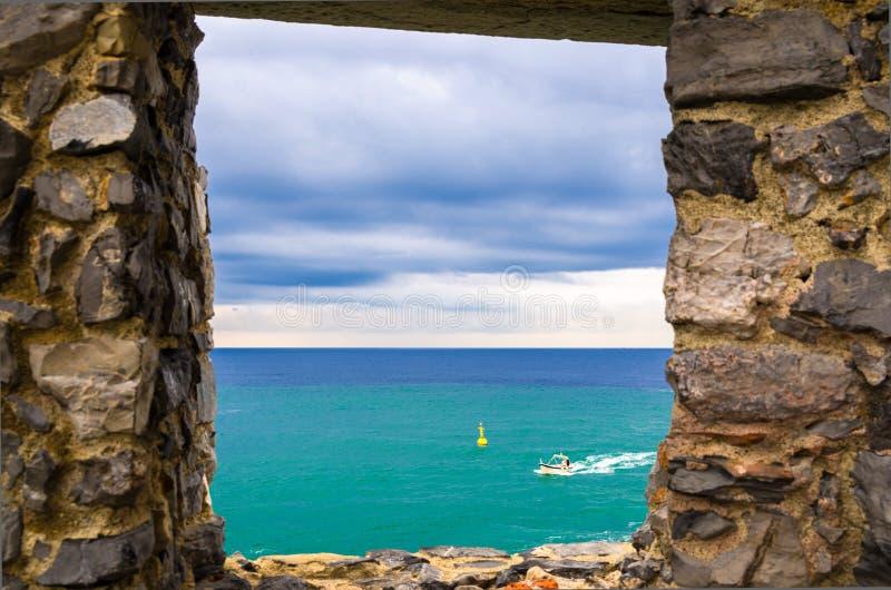 Vista de la agua de mar ligur, del acantilado de la roca de la isla de Palmaria y del barco a través de la ventana de la pared de foto de archivo libre de regalías