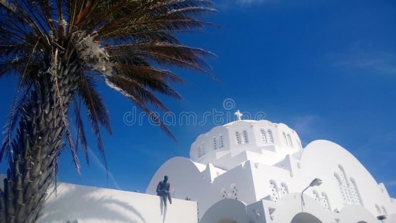 Vista de la bóveda de la catedral metropolitana ortodoxa de la ciudad de Fira en Santorini Con una palmera en el primero plano imagenes de archivo
