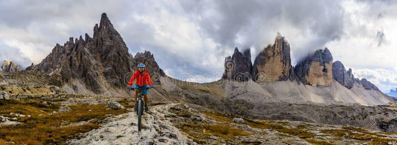 Vista de la bici de montaña del montar a caballo del ciclista en el rastro en dolomías, Tre C imagen de archivo libre de regalías