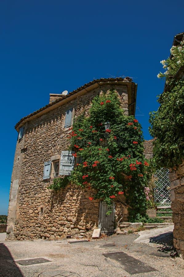 Vista de la casa de piedra típica con el cielo azul y las flores soleados, en un callejón del pueblo histórico de Menerbes fotos de archivo libres de regalías