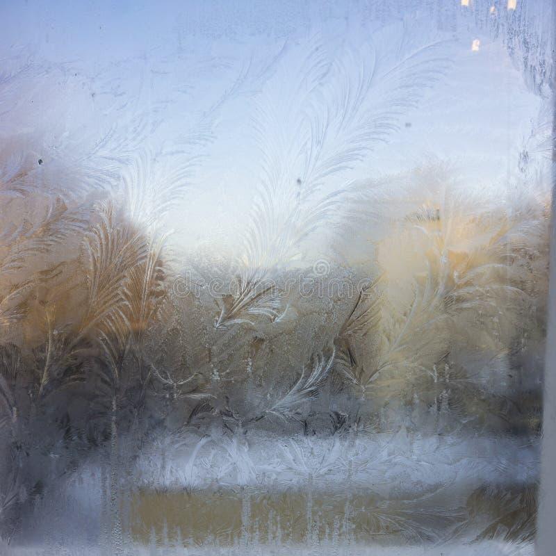 Vista de la casa vieja de la ciudad de una ventana congelada del invierno Modelos del hielo de la textura sobre el vidrio Foco se foto de archivo libre de regalías