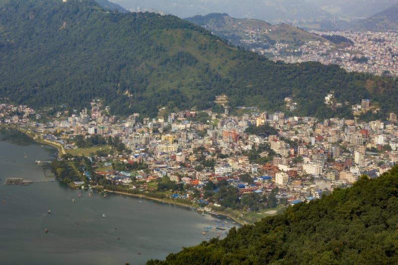 Vista de la ciudad de Pokhara cerca del lago Phewa con los barcos en el agua, contra la perspectiva de la ciudad de la montaña ve imagenes de archivo