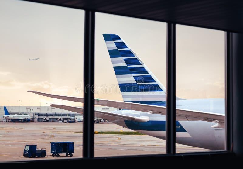 Vista de la cola del fuselaje del aeroplano con el cargo a través de la ventana en el airp imagenes de archivo