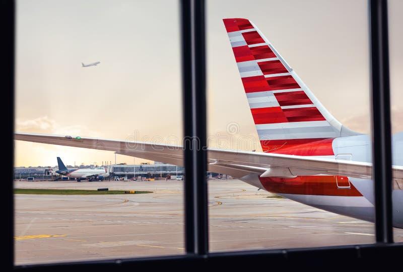 Vista de la cola del fuselaje del aeroplano a través de la ventana en el aeropuerto fotografía de archivo