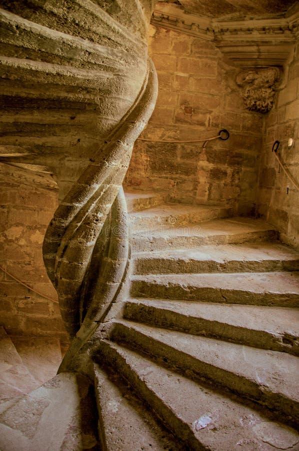 Vista de la escalera de piedra con la luz dramática en el castillo de Lourmarin foto de archivo