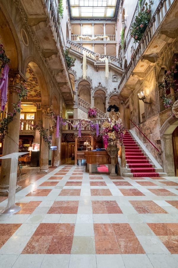 Vista de la escalera interior y de los altos arcos en el hotel antes Palazzo Dandolo de Danieli, adornada para el carnaval de Ven imagen de archivo