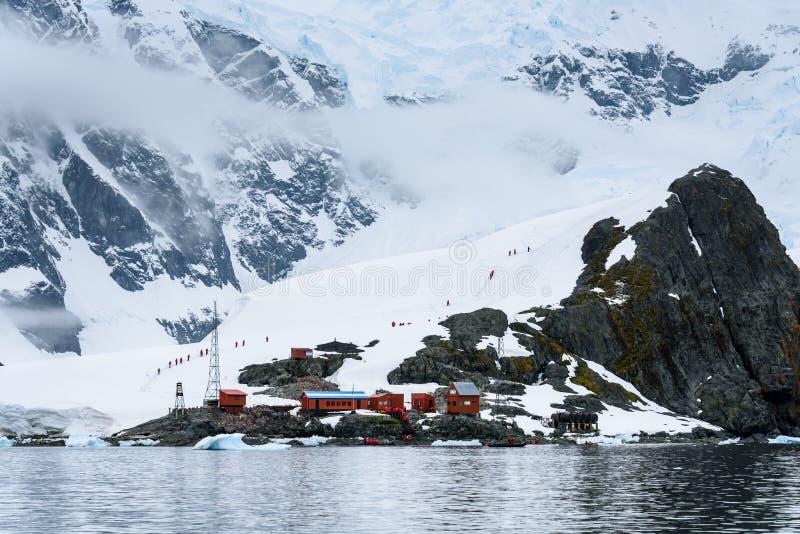 Vista de la estación de Almirante Brown del agua, línea de turistas que caminan en el fondo, puerto de Paradise, la Antártida fotos de archivo libres de regalías
