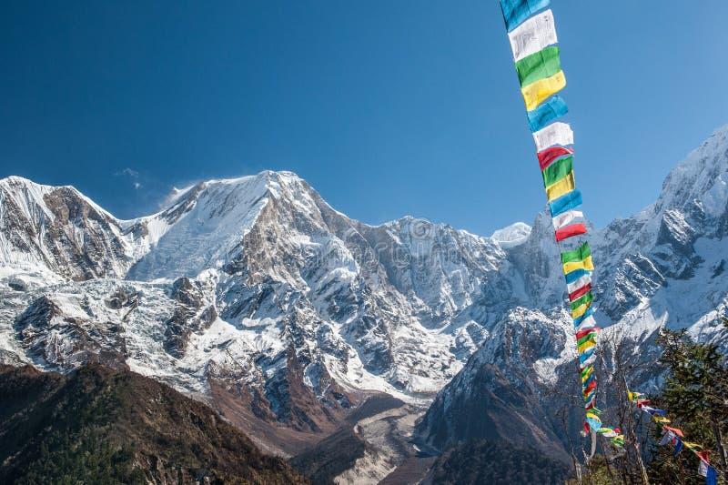 Vista de la gama nevada de soporte Manaslu y de banderas del rezo 8 156 metros con las nubes en Himalaya, día soleado en el glaci fotografía de archivo