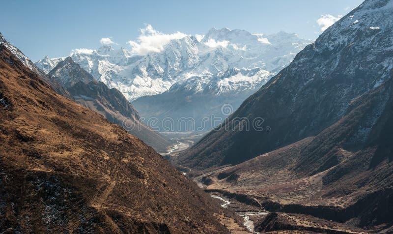 Vista de la gama nevada de soporte Manaslu y de valle en el camino para pasar 8 156 metros con las nubes en Himalaya, día soleado foto de archivo