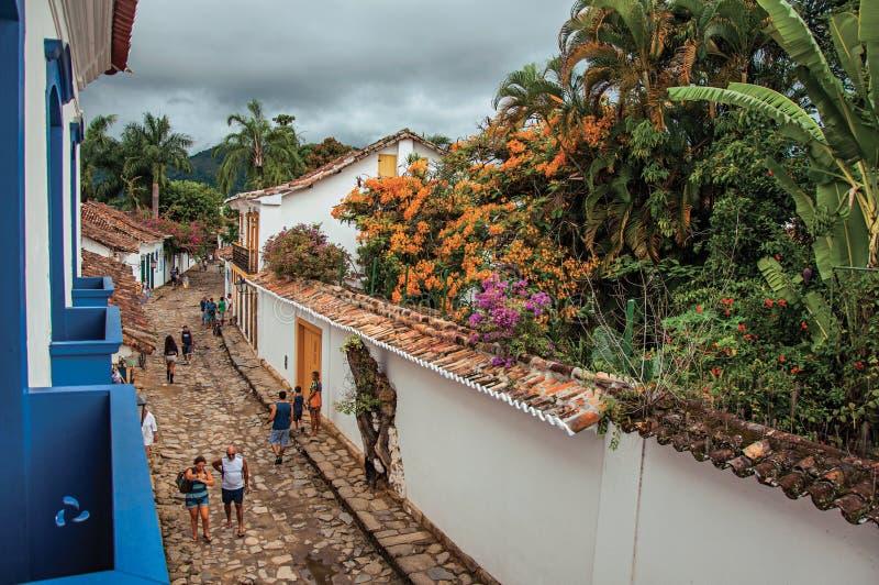 Vista de la gente en callejón con la acera de piedra y de casas viejas en Paraty foto de archivo