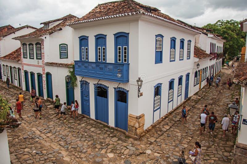 Vista de la gente en callejón con la acera de piedra y de casas viejas en Paraty imagen de archivo