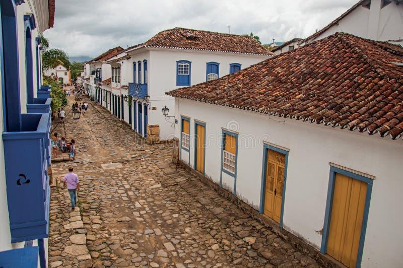 Vista de la gente en callejón con la acera de piedra y de casas viejas en Paraty imagen de archivo libre de regalías