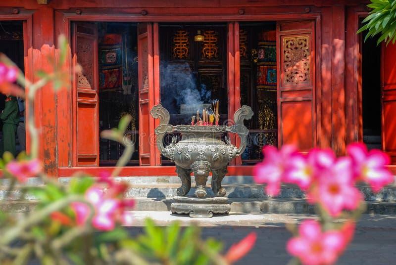 Vista de la hornilla de incienso gigante y de las puertas de madera rojas del templo de la literatura en Hanoi fotografía de archivo libre de regalías