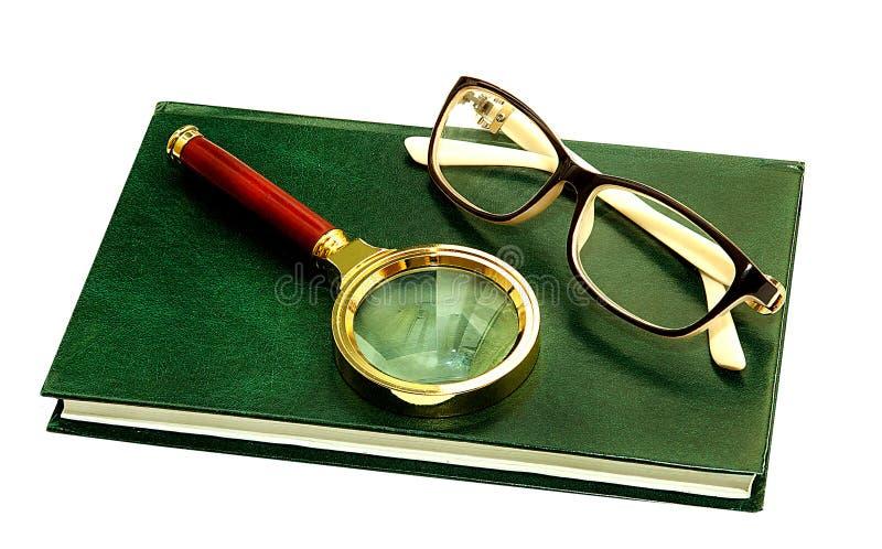 Vista de la lupa de los vidrios para ver un libro de lectura del aumento s imágenes de archivo libres de regalías