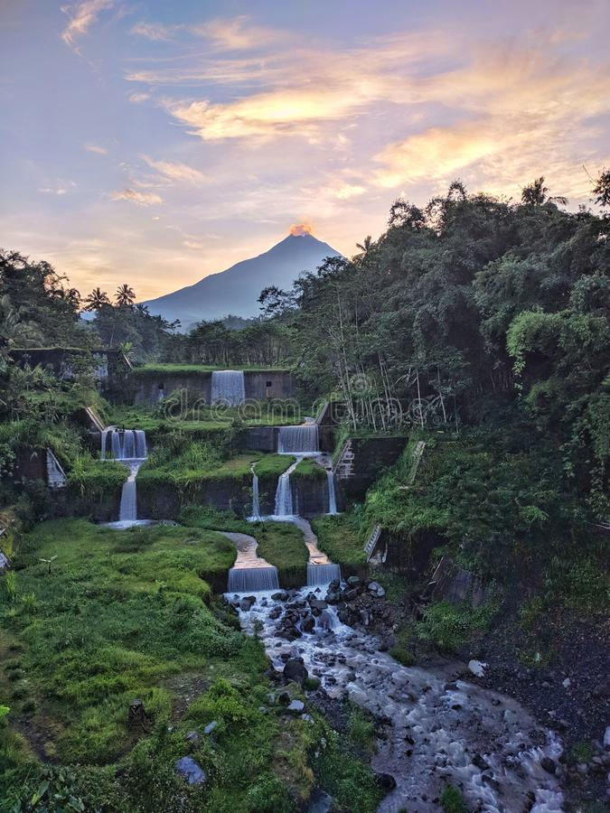 Vista de la montaña Merapi desde el puente Mangunsuko, Magelang Indonesia. Amanecer con paisaje forestal, represa y montaña fotografía de archivo libre de regalías