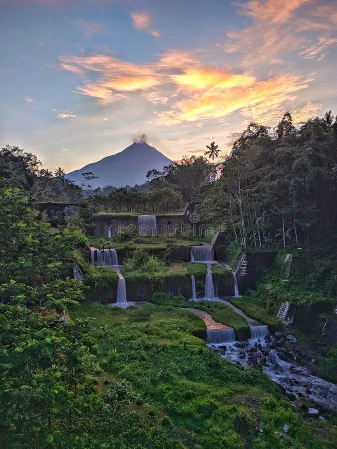Vista de la montaña Merapi desde el puente Mangunsuko, Magelang Indonesia. Amanecer con paisaje forestal, represa y montaña imagen de archivo