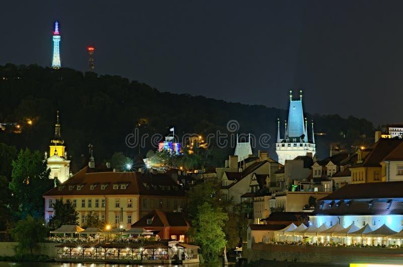 Vista de la noche Praga Río de Moldava con muchos cafés y restaurantes en los edificios en la orilla del río imagen de archivo libre de regalías