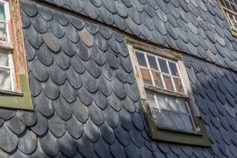 Vista de la pared alineada con las escalas de pescados pizarra-formadas, de un edificio arruinado imagenes de archivo