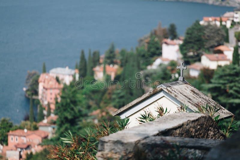 Vista de la pequeña iglesia en el pequeño pueblo de Bellano en la línea de la playa del lago del como - Lombardía imagen de archivo