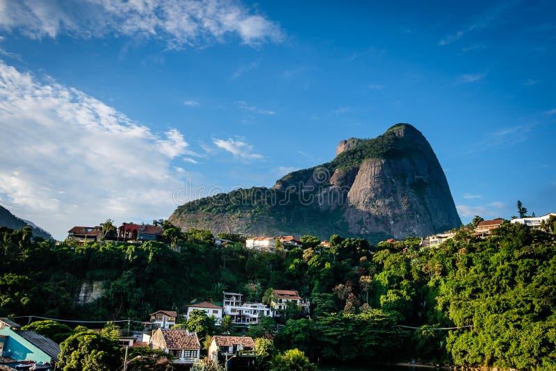 Vista de la piedra de Gavea, vista de debajo con las casas en la colina durante última hora de la tarde Barra DA Tijuca, Rio de J fotos de archivo