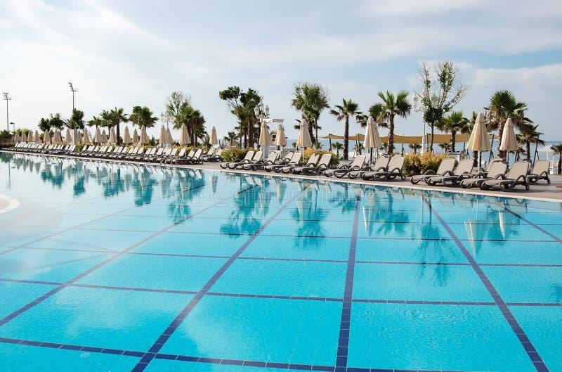 Vista de la piscina, de los paraguas y de las camas azules del sol en el lux turco fotos de archivo