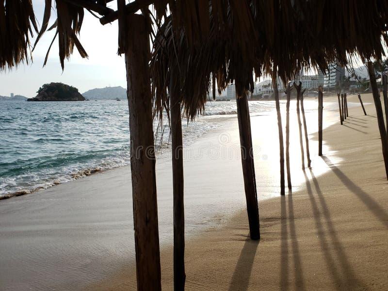vista de la playa de Acapulco de un palapa con el tejado de la palma y de ayudas de madera en un día soleado foto de archivo