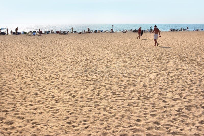 Vista de la playa Turistas, sunbeds y paraguas en día caliente del verano imágenes de archivo libres de regalías