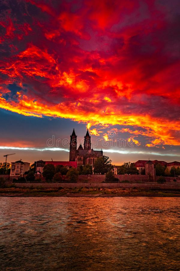 Vista de la puesta del sol sangrienta delante de la catedral en Magdeburgo, Alemania, otoño, cielo nublado rojo imagen de archivo libre de regalías