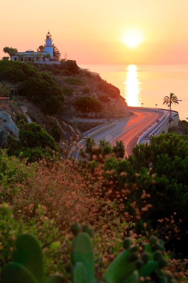 Vista de la salida del sol con el fondo del faro y del mar fotografía de archivo libre de regalías