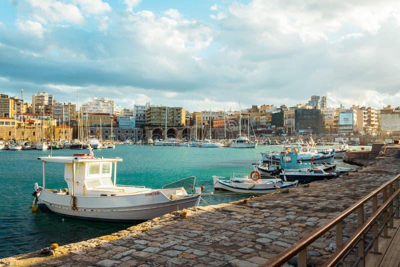 Vista de la vieja opini?n de los botes peque?os y de la ciudad del puerto de Heraklion imágenes de archivo libres de regalías