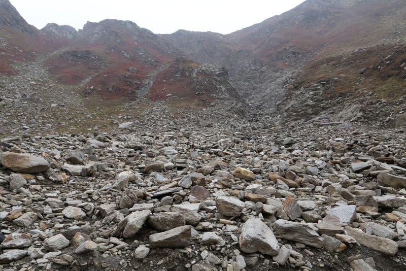Vista de las altas montañas con las rocas en el primero plano foto de archivo libre de regalías