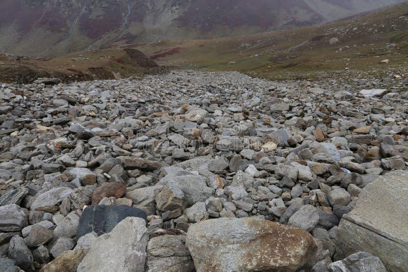 Vista de las altas montañas con las rocas en el primero plano fotos de archivo libres de regalías
