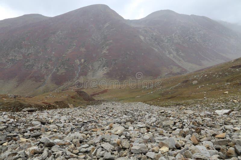 Vista de las altas montañas con las rocas en el primero plano imagenes de archivo