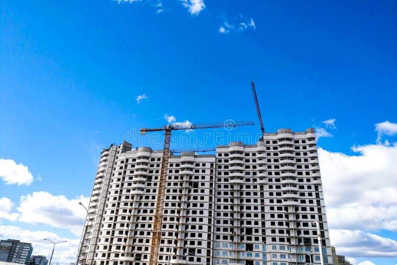 Vista de las grúas de construcción y de la nueva casa bajo construcción contra el cielo azul imagenes de archivo