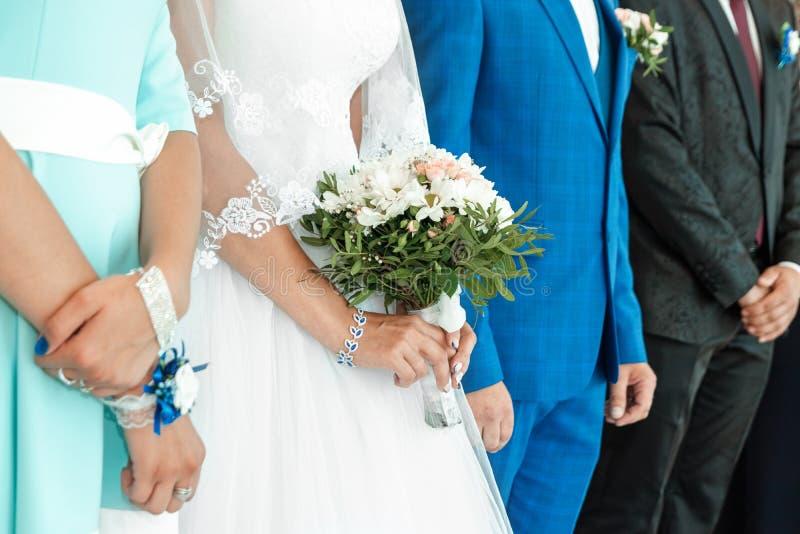 Vista de las manos de una novia y el ramo con la fiesta nupcial al fondo Concepto de matrimonio, relación familiar, fotografía de archivo libre de regalías