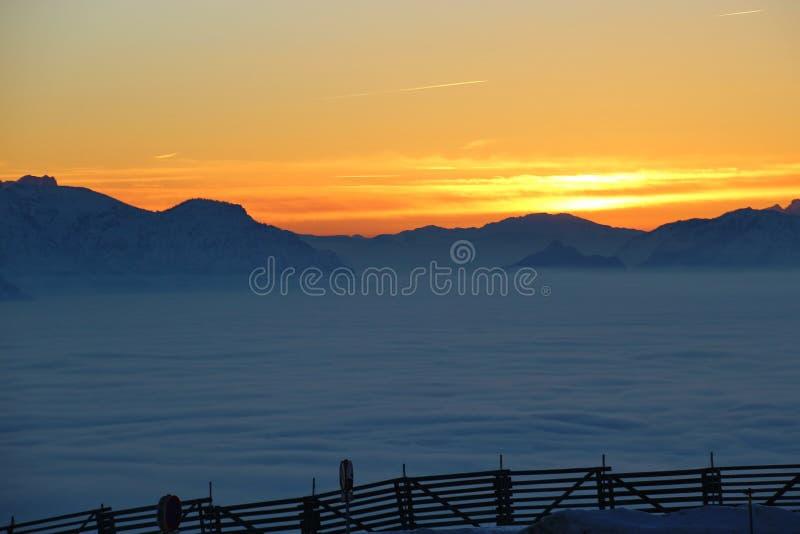 Vista de las montañas en la puesta del sol, en invierno Una capa de alta niebla sobre el valle de Salzburg, Austria imagenes de archivo