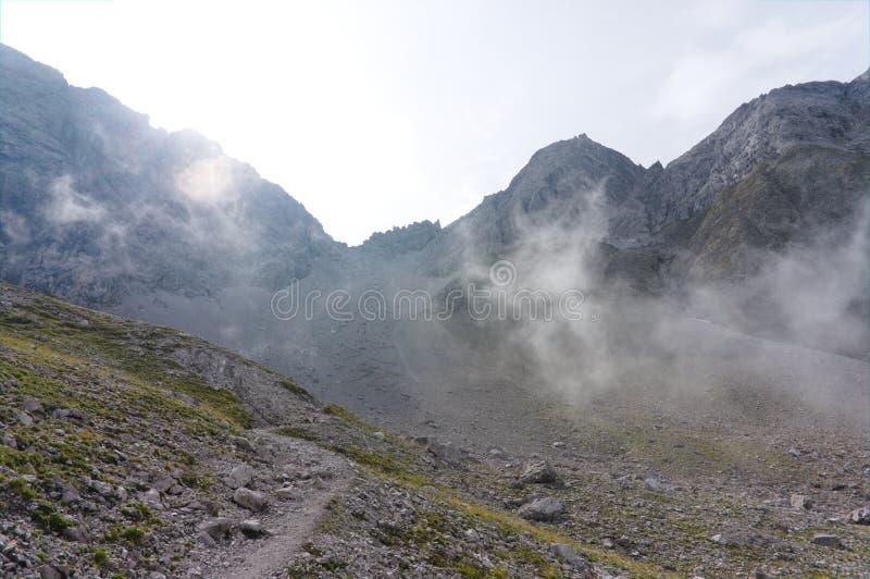 Vista de las montañas de niebla en una pista de senderismo de la mucha altitud en verano fotos de archivo