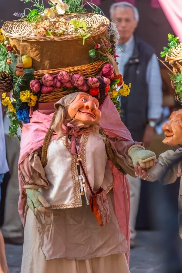 Vista de las muñecas del granjero, manipulada con la gente dentro, llevando la cesta tradicional grande, en el mercado medieval d fotos de archivo libres de regalías