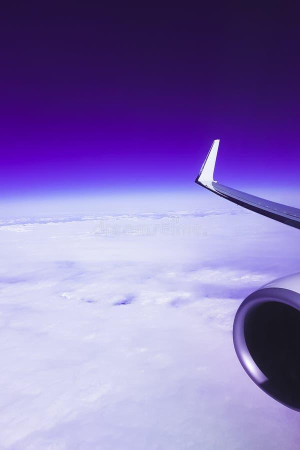 Vista de las nubes y del cielo de la ventana plana durante el vuelo, color que brilla intensamente p?rpura fant?stico fotos de archivo