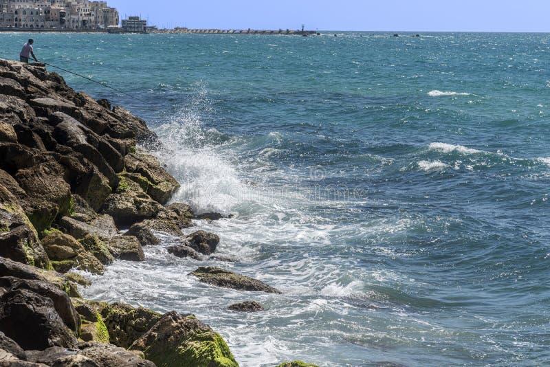 Vista de las ondas salvajes que se estrellan en las rocas en el bulevar de Tel Aviv Israel En la distancia la ciudad vieja de la  imágenes de archivo libres de regalías