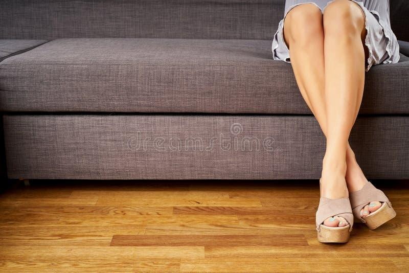 Vista de las piernas delgadas perfectas de una chica joven en cuñas de moda de madera que se sienta en el sofá imágenes de archivo libres de regalías