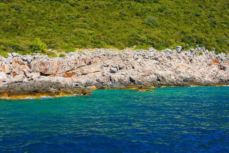 Vista de las rocas, del bosque y del mar azul fotos de archivo