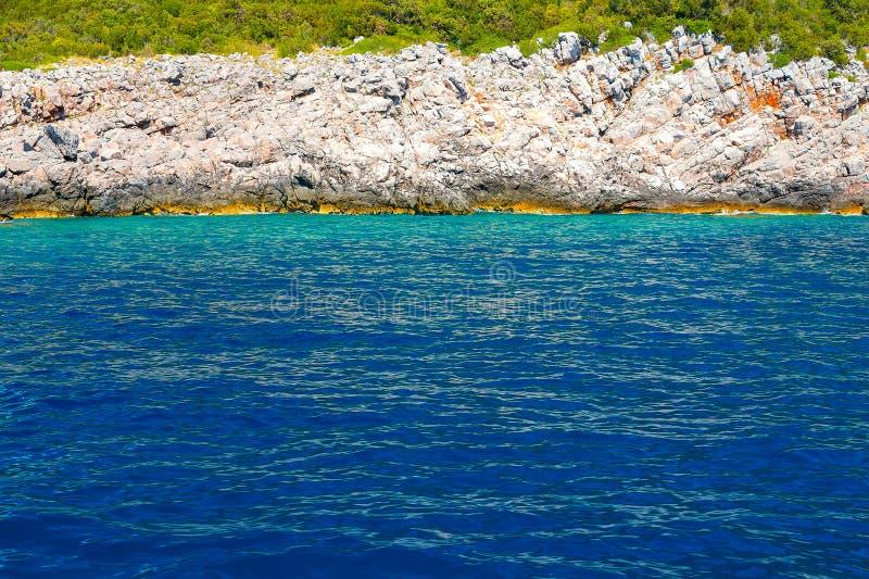 Vista de las rocas, del bosque y del mar azul fotografía de archivo