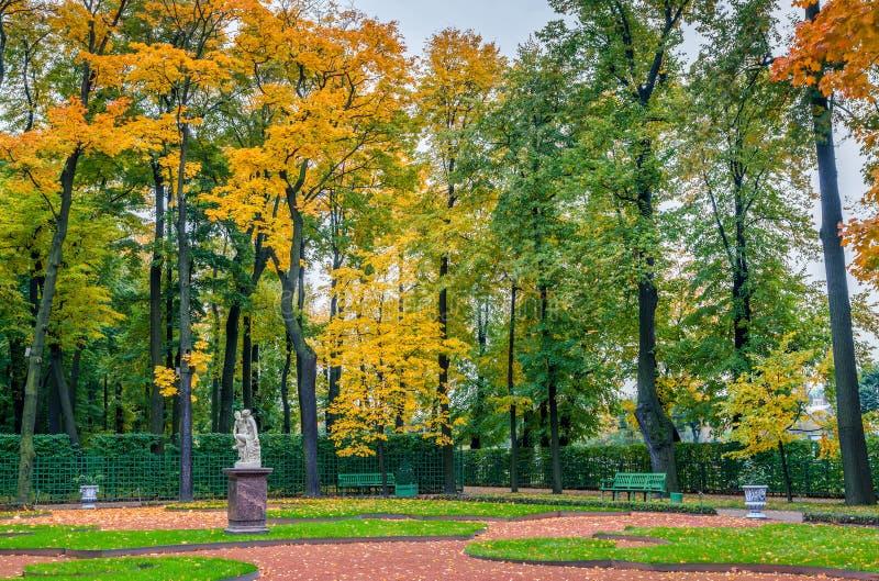 Vista de los árboles del otoño, de la estatua de mármol antigua, del césped y de los bancos adentro fotos de archivo libres de regalías