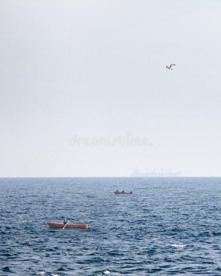 Vista de los barcos de pesca en un fondo del mar abierto azul y de un petrolero borroso en el horizonte imagenes de archivo